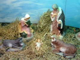The baby Jesus resting on hay between an ass and and ox and with his parents looking on.